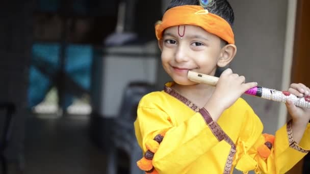 Little Lord Krishna Kanhaiya Indian God- Cute Child Playing flute looking  at camera Indian Asian cute child in traditional Hindu god Krishna outfit  playing flute