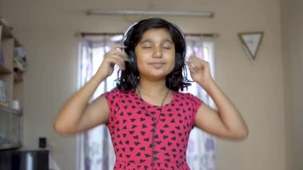 glücklich indische asiatische kaukasische Mädchen mit Kopfhörer genießen Musik hören auf mobilen nicken und tanzen Porträt Vorderansicht.