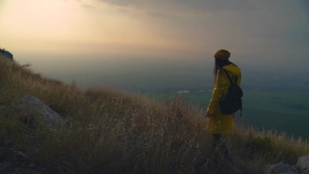 Young woman hiking walks on mountain ridge and reaches mountain summit, arms outstretched