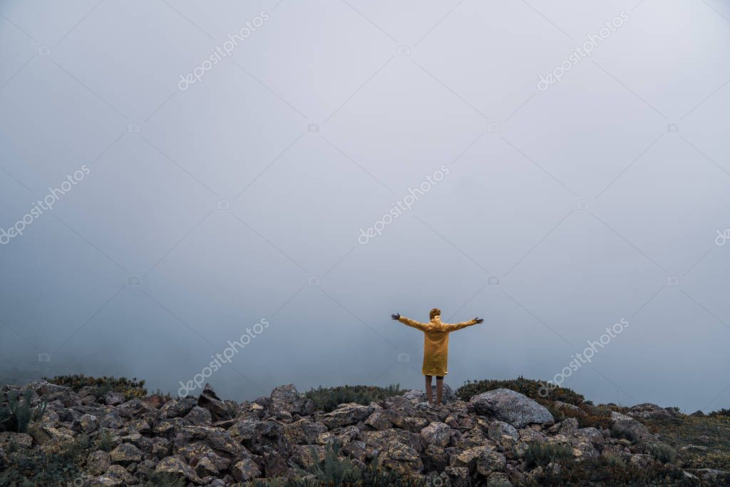 Female in yellow raincoat, jeans shorts standing at top of mountain with view of peaks at horizon. Landscape. Nature.