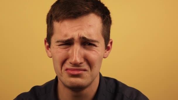 frustrovaný, muž pláče na žlutém pozadí