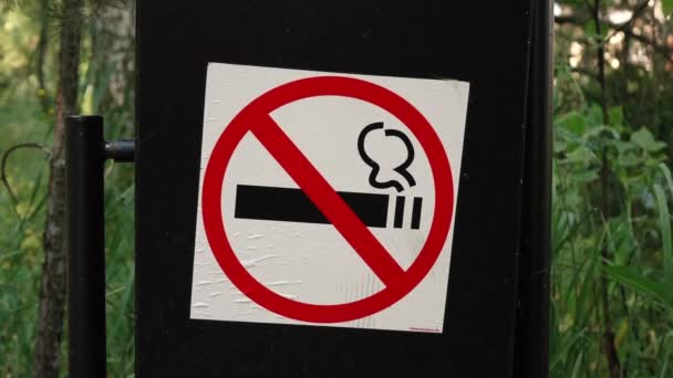Schild Rauchverbot auf schwarzem Mülleimer im Wald.