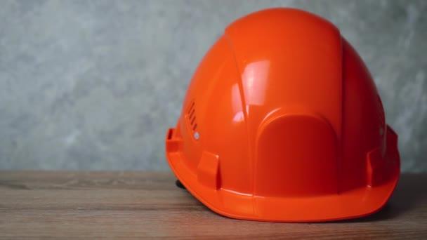 Orangefarbener Arbeitshelm liegt auf dem Tisch.
