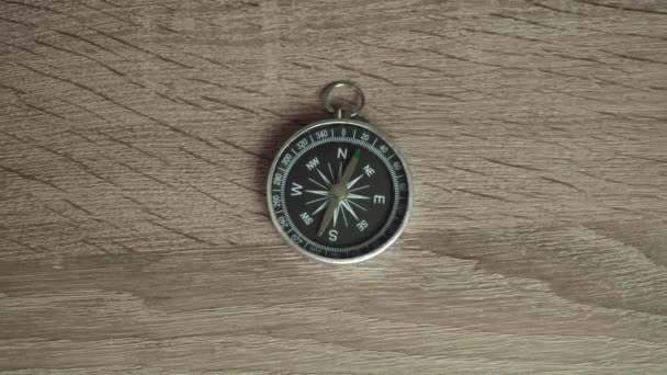 compass is on a wooden table. camera zoom