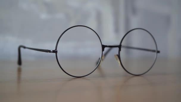 kerek szemüveg fekszik egy fa asztalon