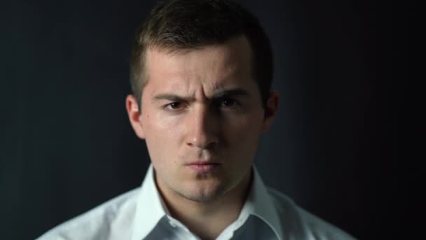 an aggressive male businessman stands and glares at the camera