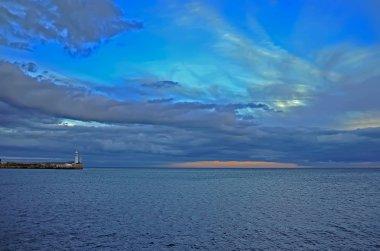 Orange sunset amid Blue-Blue autumn sky over the sea near the lighthouse at Crimea