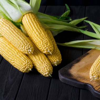 Yellow juicy corn with green leaves on a black tree table