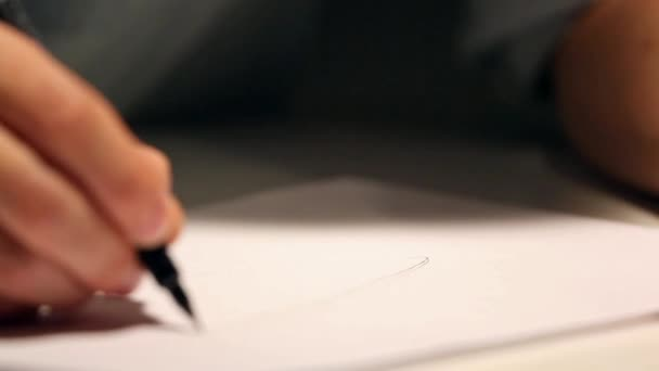 Man is drawing or writing on white sheet of paper. Macro shot of business wearing a shirt and writing on paper behind the desk