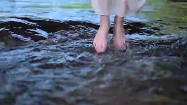 Beautiful barefoot girl dipping her feet into fresh flowing river stream