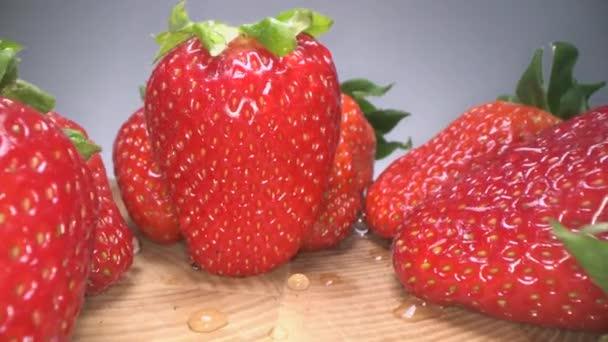 Na dřevěné pozadí se na dřevěném podkladu střídalo červené šťavnaté jahody. Sladké sklízené jahody, zdravé životní prostředí