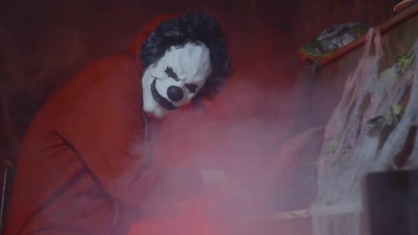 Felismerhetetlen ember ijesztő bohóc Halloween maszkot zongorázni misztikus köd és a sütőtök a háttérben. Ijesztő halloween party a teljesítmény éjjel