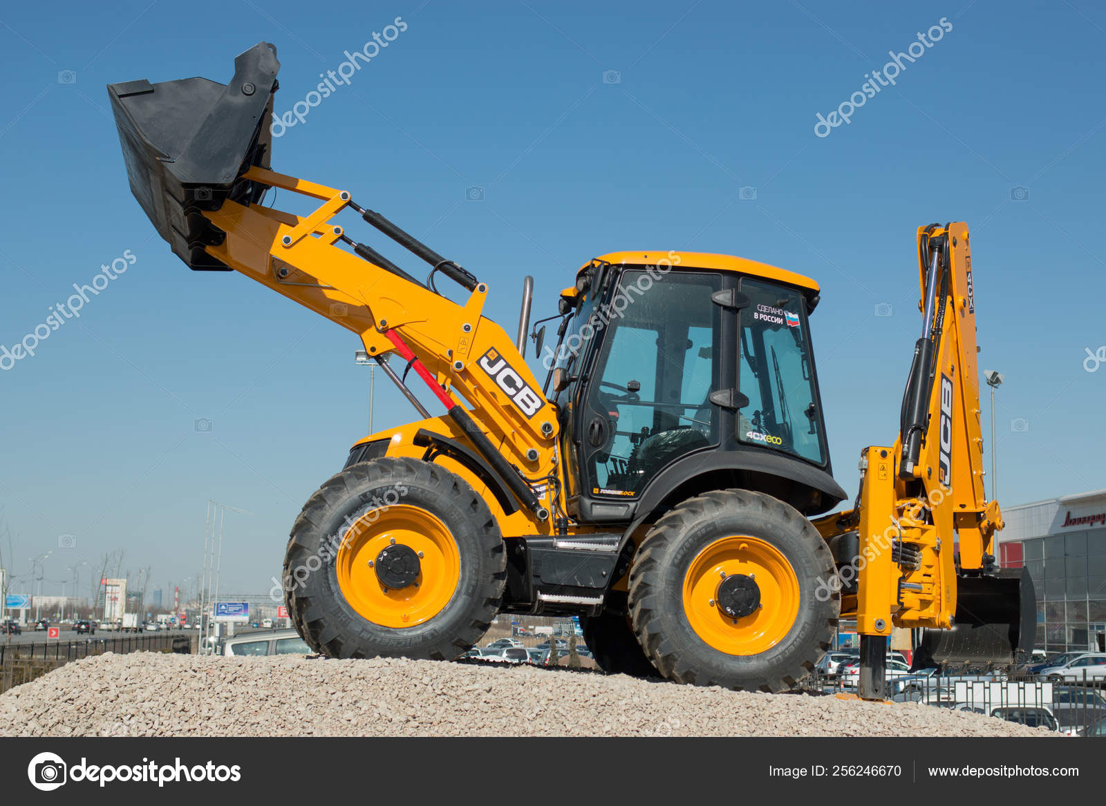The JCB backhoe loader stands on the advertising stand in