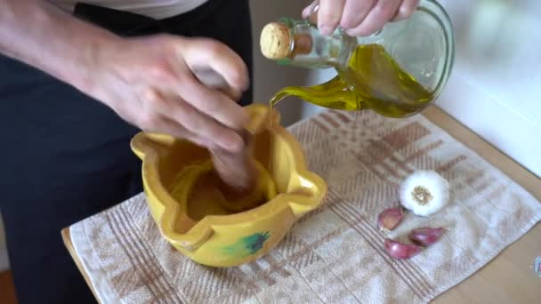 Close-up of chef preparing allioli sauce by hand with a mortar and pestle. Catalan typical sauce