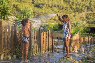 Black mother and his son playing in the garden with hose in summer. Lifestyle concept