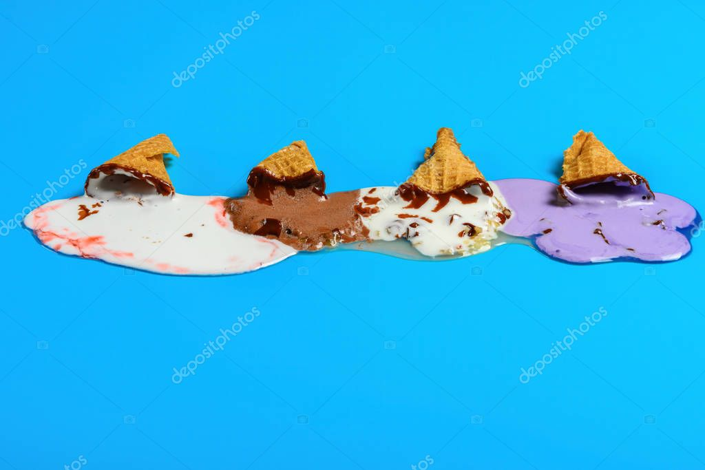front view multiple flavor ice cream cones melted on blue background