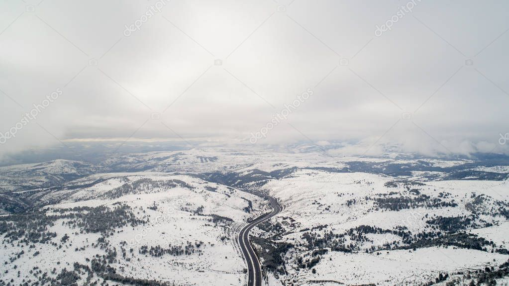 Aerial view of  winter asphalt highway or motorway road in countryside with cars and cargo logistic trucks in winter time. Winter Landscape