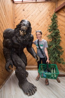 JULY 11 2017 - KLAMATH, CA: An adult female holding a shopping basket at the Tree of Mystery gift shop stands next to a giant Bigfoot / Sasquatch statue inside the store located in the Redwoods