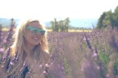 Photo Portrait of Blonde adult woman in a lavender field, smiling, in the golden hour before sunset