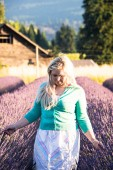 Photo Portrait of Blonde adult woman stands in a lavender field, smiling, in the golden hour before sunset