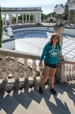 San Simeon, California - August 7, 2018: Female tourist poses on the steps outside the Hearst Castle, near the Neptune Pool. Pool is drained and has no water
