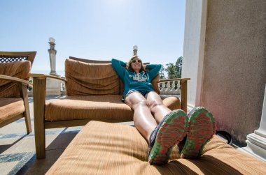 San Simeon, California - August 7, 2018: Woman tourist sits and relaxes in the patio chairs on the deck of the Neptune Pool at the Hearst Castle