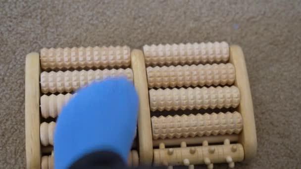 Žena s plantážovou fasciidou používá dřevěný váleček se špičkami k masáži její bolavé nohy