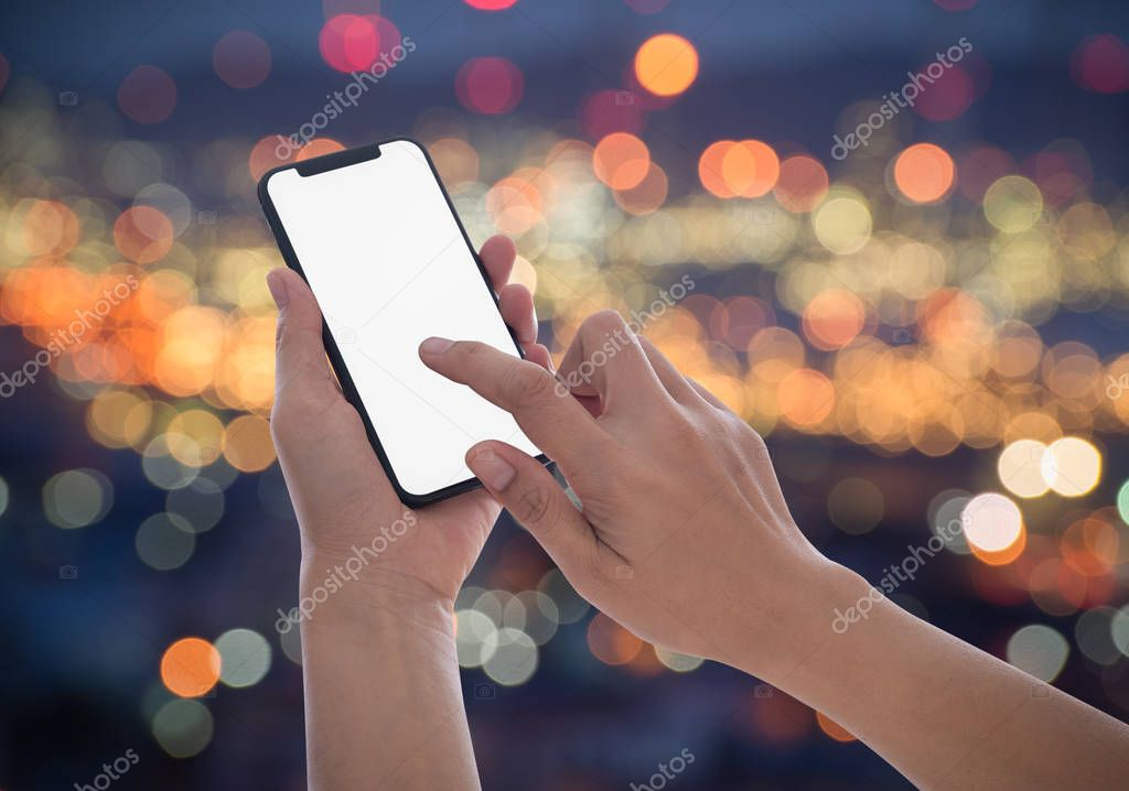 Close-up image of male hands using smartphone at night on city shopping street, searching or social networks concept, hipster female typing an sms message to his friends