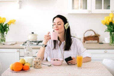 Young beautiful woman using enjoying music and coffeewhile healthy breakfast in light modern kitchen.
