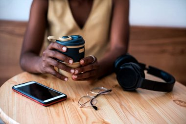Pretty young black girl listening to music on smartphone at cafe. She drinks fresh hot coffee at reusable cup.