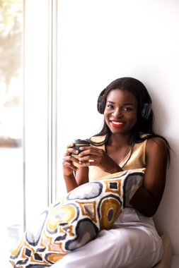 Smiling black girl listening to music and drinking coffee at cafe. She is sitting at windowsill and drinking coffee from reusable cup.