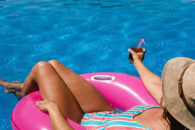 Young woman with hat and swimsuit in a blue pool. Pretty girl on a pink float enjoying the summer while having a cocktail.