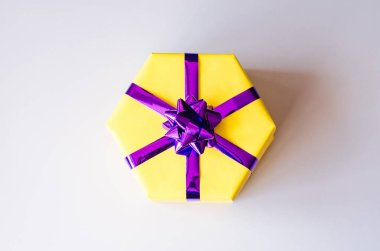 Yellow gift box with a purple bow.