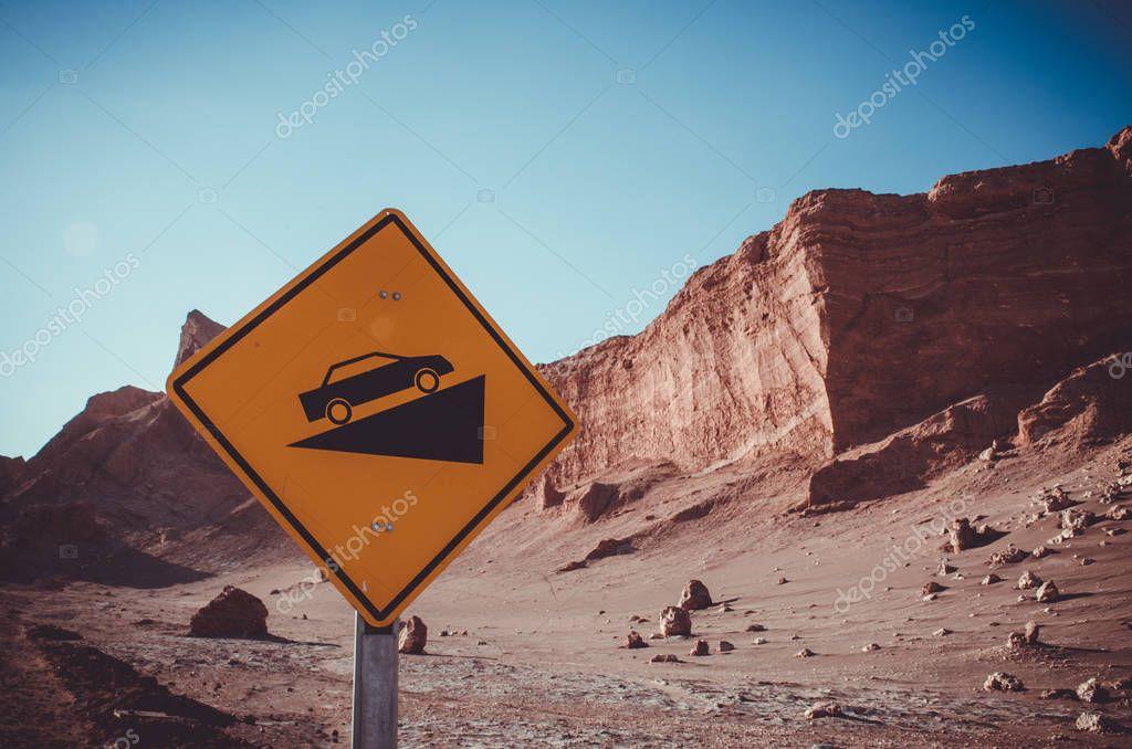 Desert crests following big slope car signal in Atacama, Chile