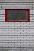 Régi fal fehér tégla piros keretben egy üvegezett ablak.