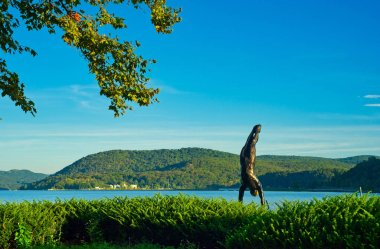 PEEKSKILL, NY - SEPTEMBER 4, 2018: A bronze statue of a diver in this city's scenic Riverfront Green Park appears to be taking a dive into the Hudson from the angle of view.