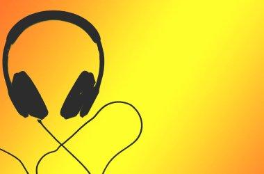 Black headphones isolated on yellow background. Selective focus of headphone.