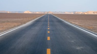 Car traveling on road in the middle of gobi desert in Dunhuang Yardang National Geopark, Gansu, China
