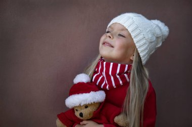 Happy little girl smiling with a Christmas bear. Happy girl holding a Christmas bear.