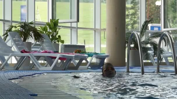 legrační malá holka baví v aquaparku. Zpomalený pohyb