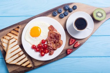 Breakfast with eggs, bacon, tomatoes, coffee and berries