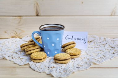 blue mug of tea and oatmeal cookies on wooden background