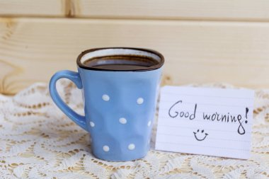 blue coffee mug with white dots and note good morning on a wooden background