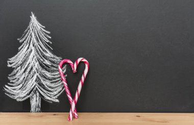 Christmas Tree Drawing on Black Chalkboard with Heart Shaped Candy Sticks