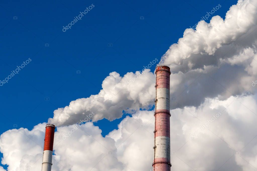 Smoking chimney against a clear sky, close-up.
