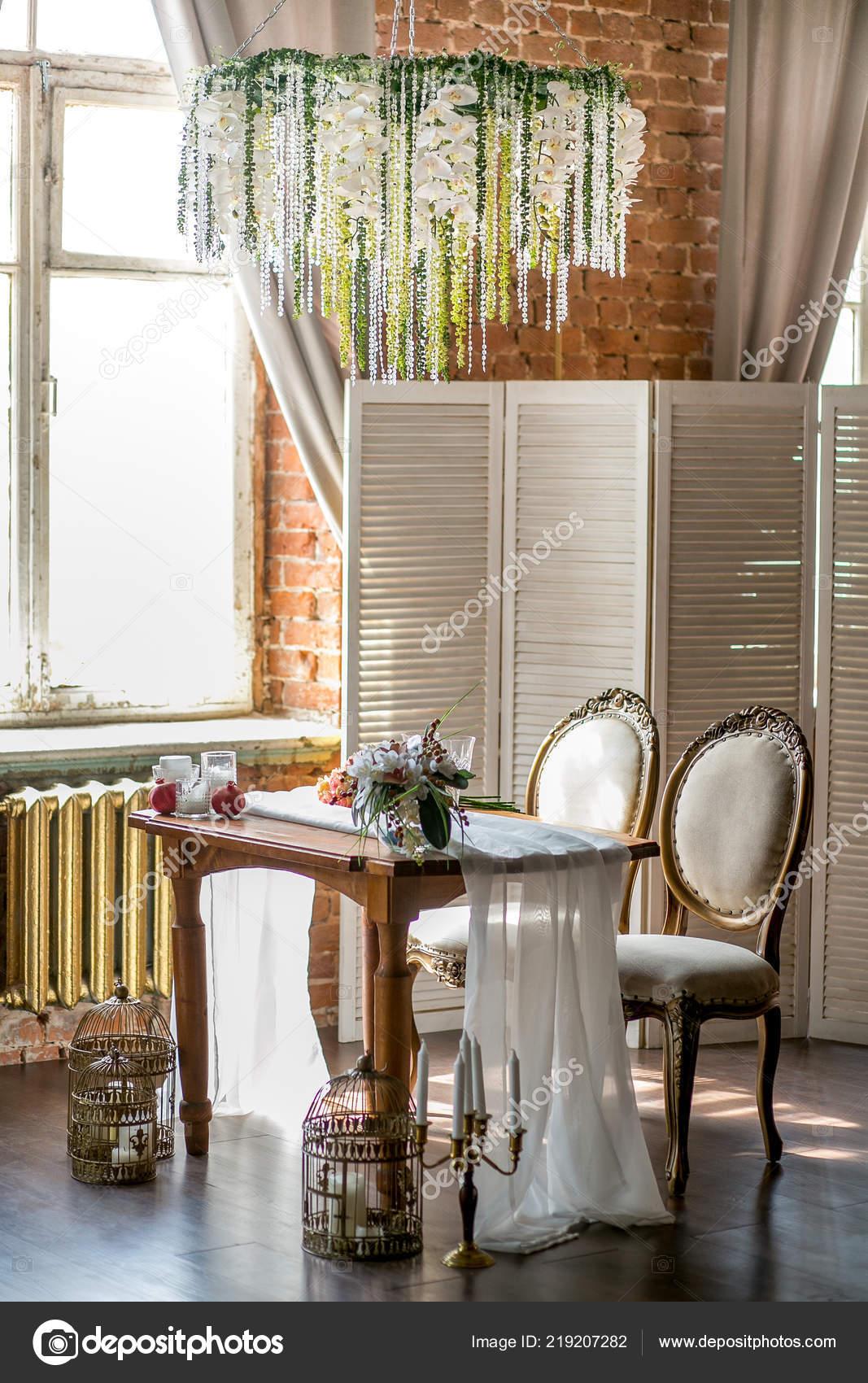 Tavolo da pranzo con sedie classiche, lampadario di fiori ...