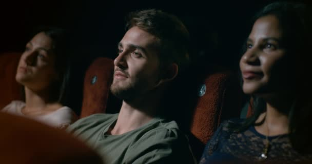 junger Mann sitzt in einem belebten Kino und schaut sich einen Film an.