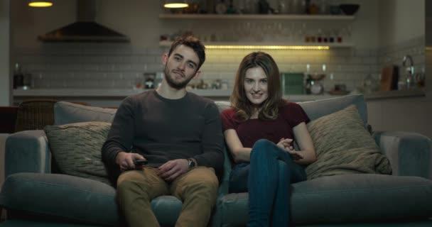 Nettes Paar wechselt während einer gemütlichen Nacht vor dem Fernseher die Kanäle.