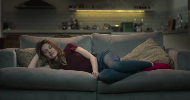 Žena leží pohodlně na pohovce se dívat na televizi.