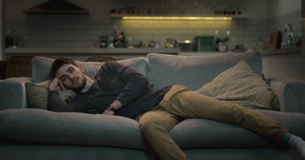 Uvolněný člověk pohodlně ležet na pohovce se dívat na televizi